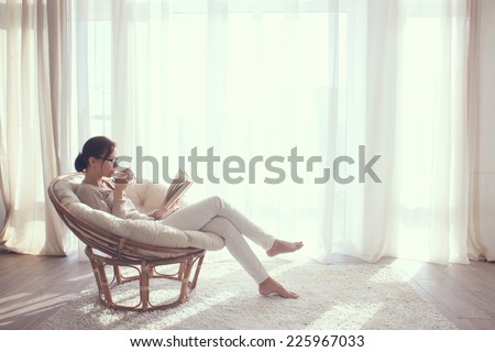 Young woman at home sitting on modern chair in front of window relaxing in her living room reading book and drinking coffee or tea #225967033