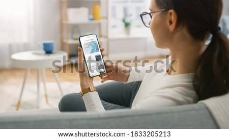 Young Woman at Home Uses Smartphone for Scrolling and Reading News about Technological Breakthroughs. She's Sitting On a Couch in Her Cozy Living Room. Over the Shoulder Shot Stock foto ©