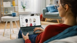 Young Woman at Home Using Laptop Computer for Browsing Through Online Retail Shopping Site. She's Sitting On a Couch in His Cozy Living Room. Over the Shoulder Camera Shot