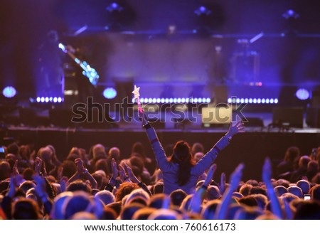 young woman at live concert and many people