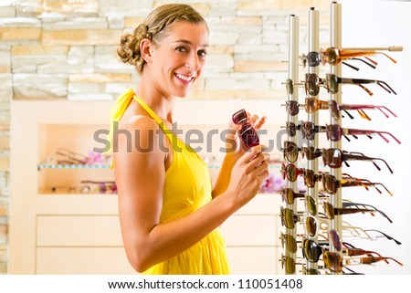 Young woman at optician with glasses, she might be customer or salesperson and is wearing sunglasses