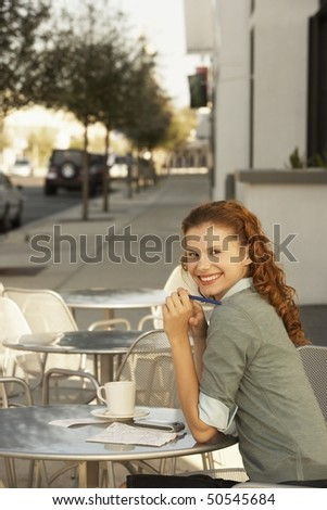 Young woman at outdoor cafe, portrait - stock photo
