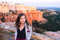Young woman at Paria view overlook with sunset over hoodoos rock formations in Bryce Canyon National Park leaning on railing