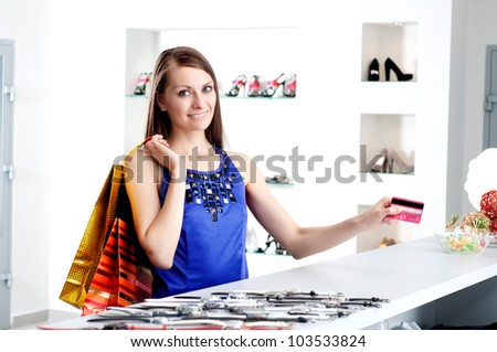 Young woman at shopping mall checkout counter paying through credit card