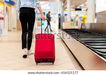 Young woman at the conveyor belt area carrying her trolly bag.