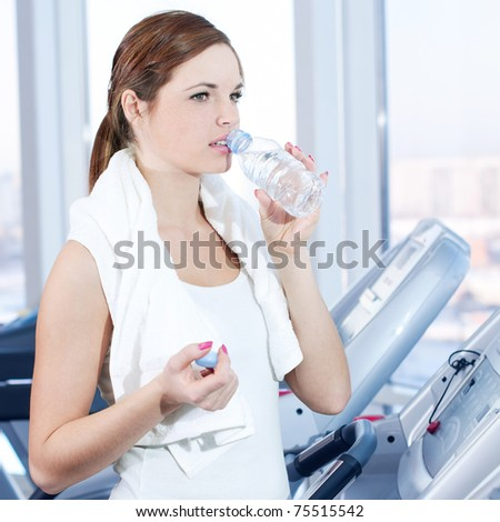 Young woman at the gym exercising. Run on on a machine and drink water - stock photo