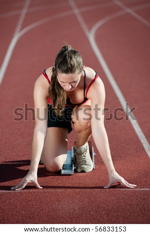 Young woman at the start of a running track