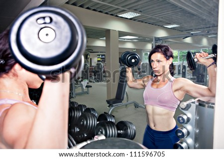 young woman at weightlifting in a gym