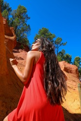 young woman back admiring orange and yellow ochre in Roussillon, France