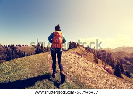young woman backpacker hiking...