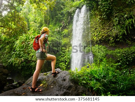 young woman backpacker looking at the waterfall in jungles.