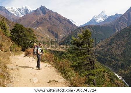 Young woman backpacker tourist standing looking Ama Dablam mountain snow peaks above deep canyon river. Everest Base Camp trekking route trail, Nepal traveling tourism. #306943724