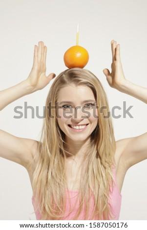 Young woman balancing orange on head