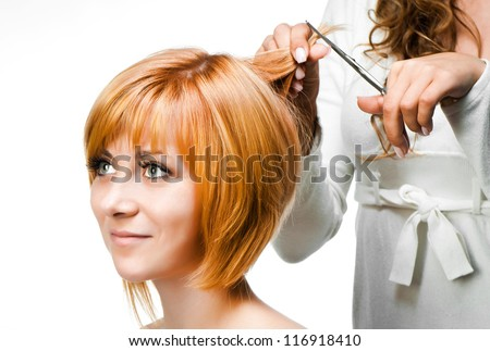 Young woman barber makes hairstyle for a girl close up