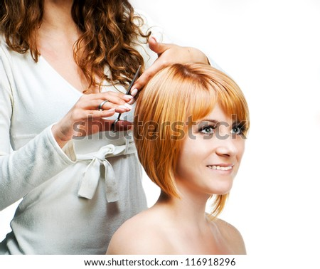 Young woman barber makes hairstyle for a girl isolated on white background