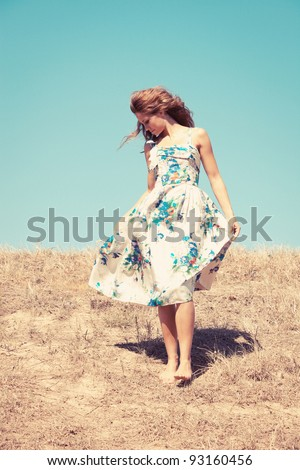 young woman barefoot in silk dress on top of the hill  sky in background, retro colours, grain added