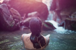 Young woman bathing and relaxing in wild lake near waterfall in the forest. toned photo