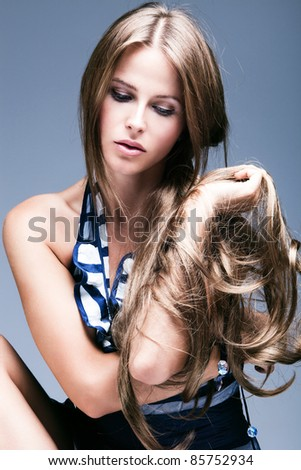 young woman beauty portrait with long blond hair, studio shot, vertical