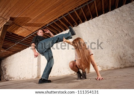 Young woman being kicked by Caucasian male