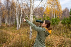 Young woman birdwatcher with binoculars in the autumn forest. Birdwatching, zoology, ecology. Research, observation of animals. Ornithology