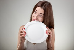 Young woman bites empty plate. Hungry woman with plate in studio on white background