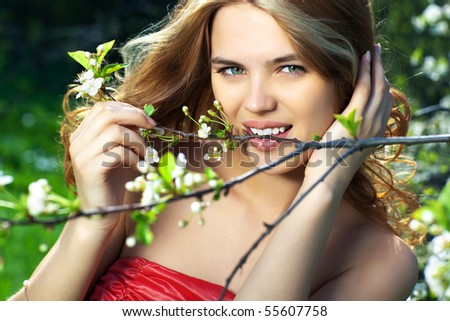 Young woman biting small branch outdoors portrait.