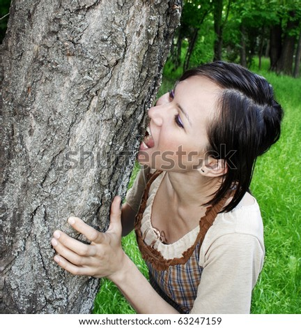 Young woman biting the tree bark