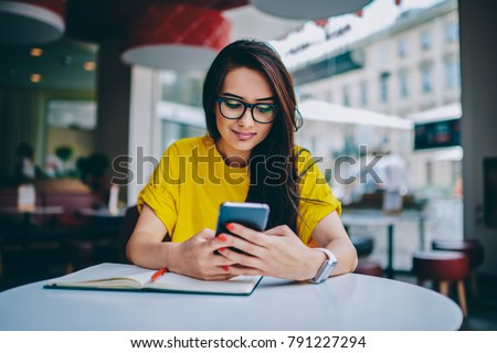 Young woman blogger in spectacles publishing new post on own website and installing new application for editing photos in social networks on digital smartphone device connected to free 4G internet