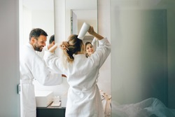 Young woman blow-drying hair with boyfriend standing next to her in bathroom