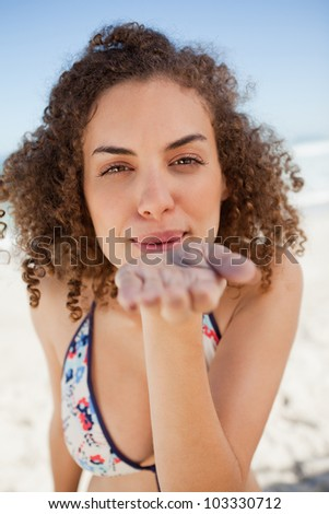 Young woman blowing a kiss while staring at the camera and standing on the beach
