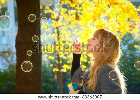Young Woman Blowing Bubbles on a bright yellow leaves background