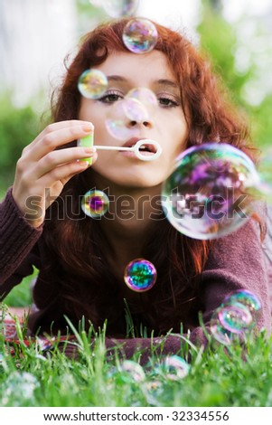 Young woman blowing bubbles on nature. - stock photo