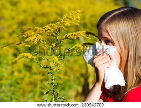 Young woman blowing nose in handkerchief because of allergy.