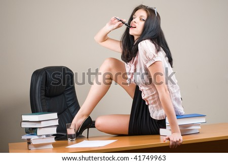 Young woman-boss sitting behind table
