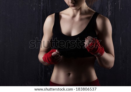 young woman boxer in red and black clothes  ready to fight  on dark grey background