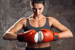 Young woman boxer wearing boxing gloves together standing isolated on wall looking down ready