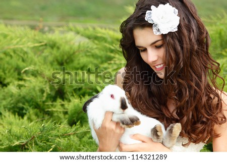 Young woman bride smiling and holding two cute rabbits over park summer nature outdoor, Alice in Wonderland