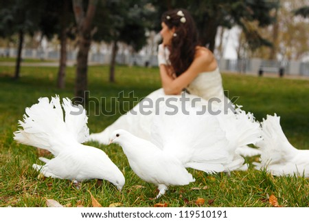 Young woman bride smiling with white pigeons over park autumn outdoor