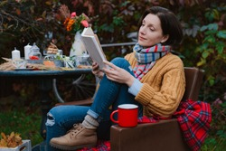 young woman brown coat sits chair at table reading book with plaid thrown over her head open air against autumn reddened foliage. autumn fashion season. Rest, tranquility, backyard, patio, melancholy