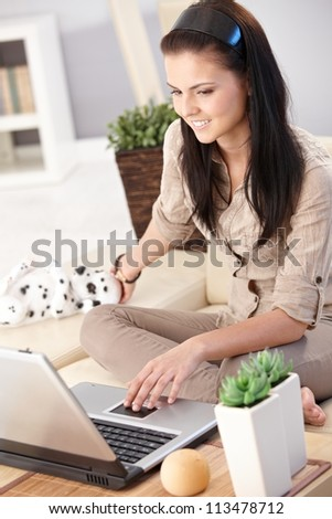 Young woman browsing internet on computer, sitting on sofa at home.