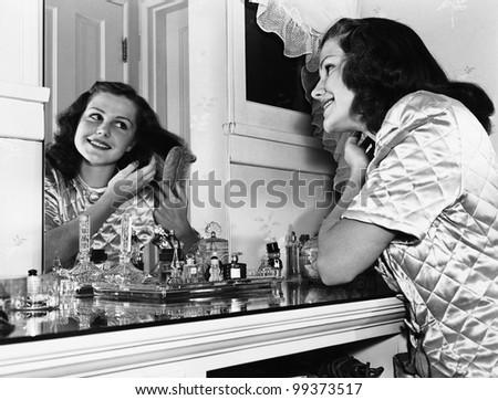 Young woman brushing hair at dressing table
