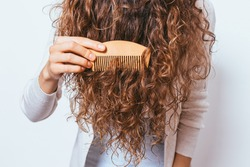 Young woman brushing her curly hair with wooden comb, close-up.