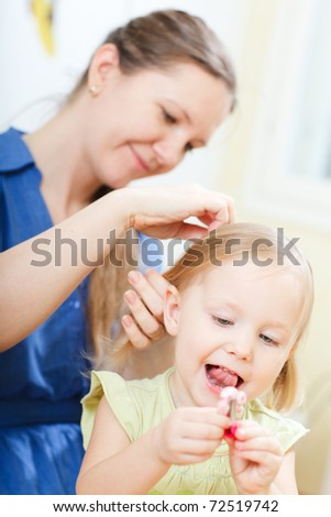 Young woman brushing her daughter's hair - stock photo