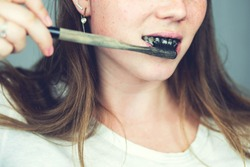 young woman brushing her teeth with a black tooth paste with active charcoal, and black tooth brush on white background for Teeth whitening clean