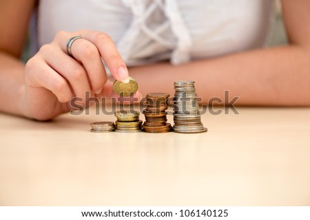 Young woman building coin-stacks like graph