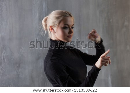 Young woman, business style. Points her finger at the invisible interface,  for design with modern interfaces, HUD and augmented reality #1313539622
