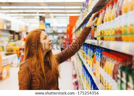 Young woman buying juice in the supermarket