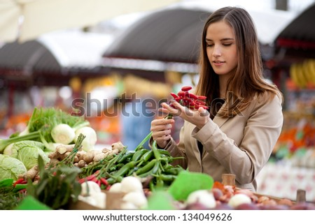 Young woman buying red hot chili peppers at the market