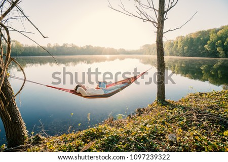 Young woman by the lake hanging on hammock reading on digital tablet one the morning. People relaxation travel technology concept
