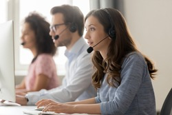 Young woman call center agent operator telemarketer in wireless headset talking consulting online client using computer working in customer service support helpline helpdesk telesales office
